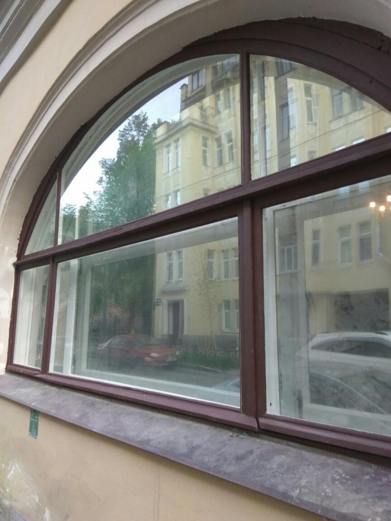 Большое арочное деревянное окно после реставрации, вид с улицы